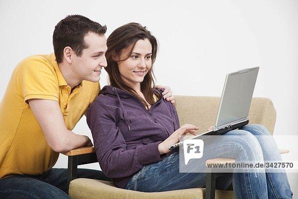 Junges Paar mit Laptop  lächelnd.