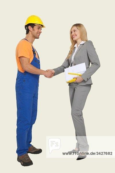 Bauarbeiter und Architekt beim Händeschütteln