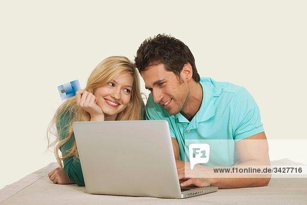 Paar liegend und mit Laptop  lächelnd