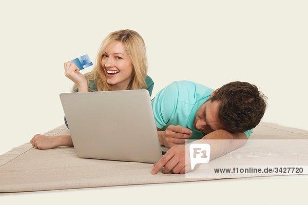 Paar liegend mit Laptop  Mann schlafend und Frau mit Kreditkarte
