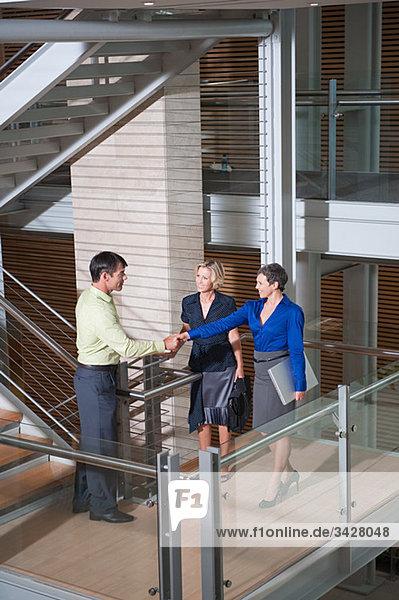 Geschäftsleute beim Händeschütteln im Treppenhaus