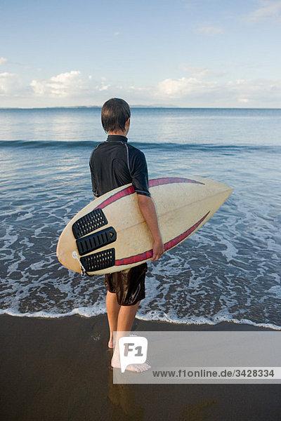 Auckland  junger Mann mit Surfbrett am Muriwai Beach