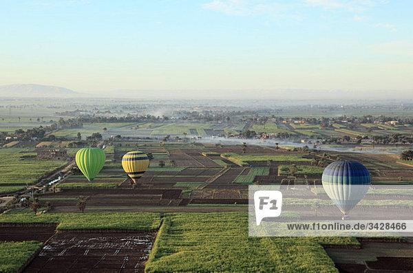 Heißluftballons über Felder bei Luxor
