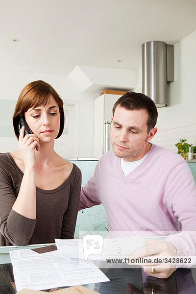 Paar am Telefon mit Rechnungen