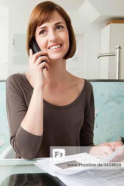 Frau am Telefon mit Rechnungen