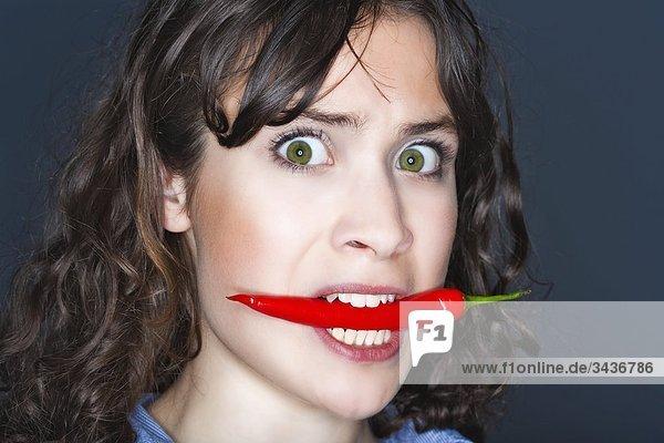 Frau hält Chili im Mund