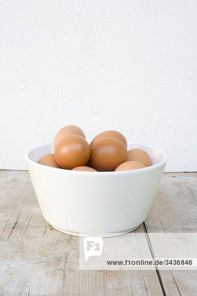 Weiß Schüssel mit braune Eier auf Holzbrett