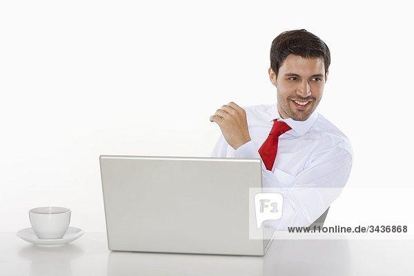 Business Executive in weißen Hemd hinter Schreibtisch mit laptop