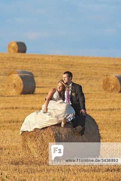 Neu-Mi Paar in ihre Hochzeit Kleider im Feld von Heu