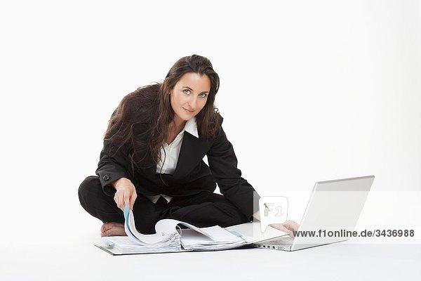 Eine junge geschäftsfrau arbeiten mit Laptop-Computer und Dateien