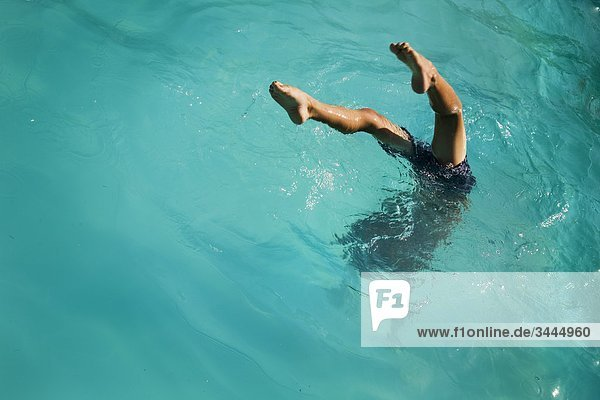 Boy diving into turquoise water  Sweden.