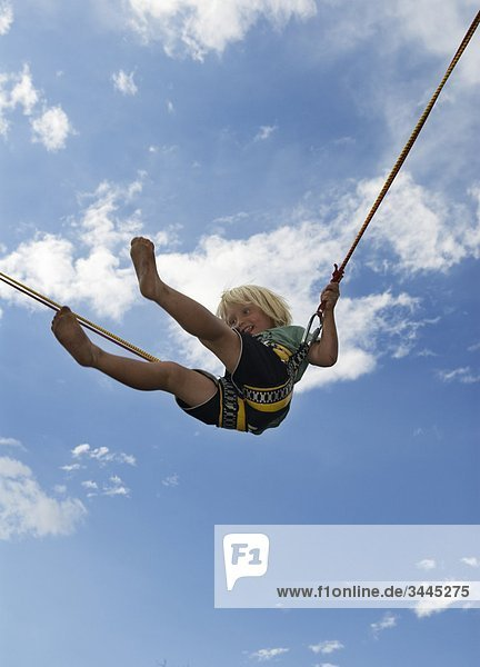 Scandinavia, Sweden, Ostergotland, Linkoping, Boy playing on bungee jumping, low angle view ets18762