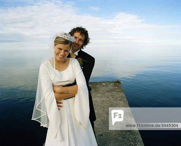 Skandinavien  Schweden  Oland  Bräutigam und Braut umarmen am Bootssteg  Lächeln  portrait
