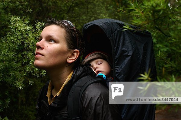 A woman with her sleeping baby in the forest