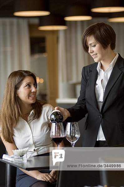 Waitress serving wine to woman at table  smiling