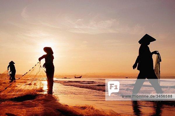 Three women in traditional hats on Mui Ne Beach  Vietnam Fishing at sunrise