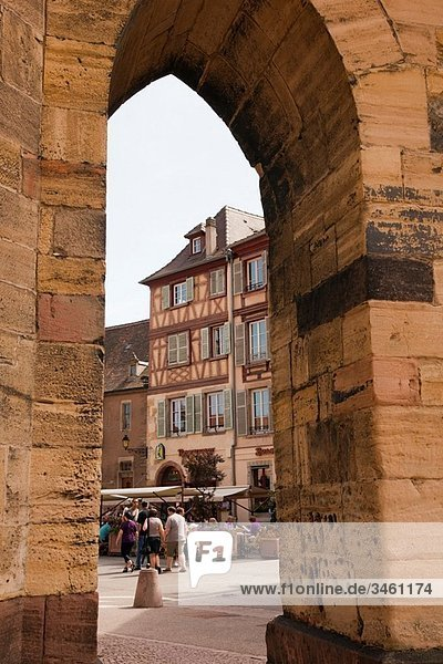 Place de la Cathedrale  Colmar  Alsace  France  Europe View through stone arch in city square