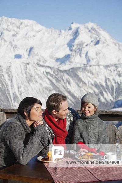 Paar und Tochter beim Essen auf dem Balkon im Skigebiet