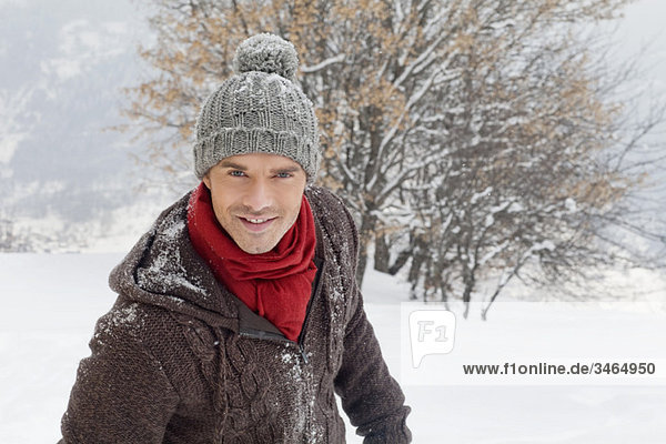 Young man in winter clothes smiling at camera