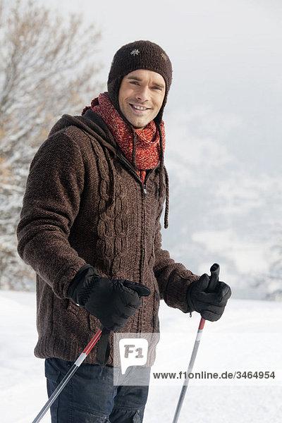 Männlicher Skifahrer lächelt vor der Kamera