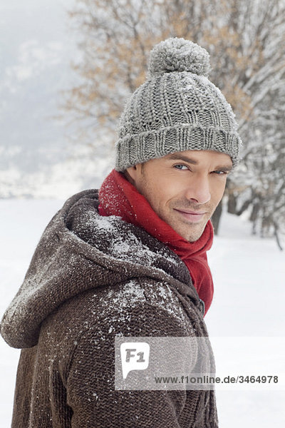 Young man in winter clothes looking at camera