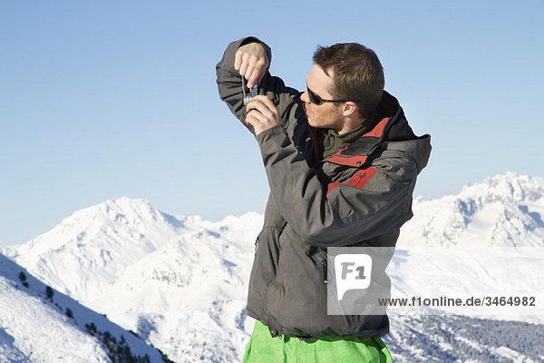 Junger Mann in Skibekleidung beim Fotografieren