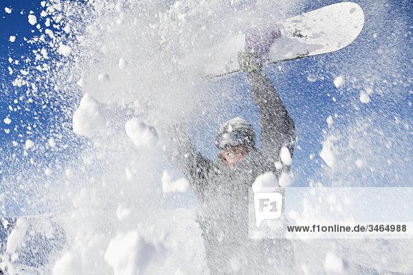 Junger Mann hält sein Snowboard über dem Kopf.