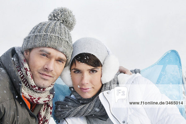 Young couple in winter clothes looking at camera