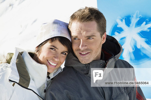Young couple in winter clothes smiling at camera