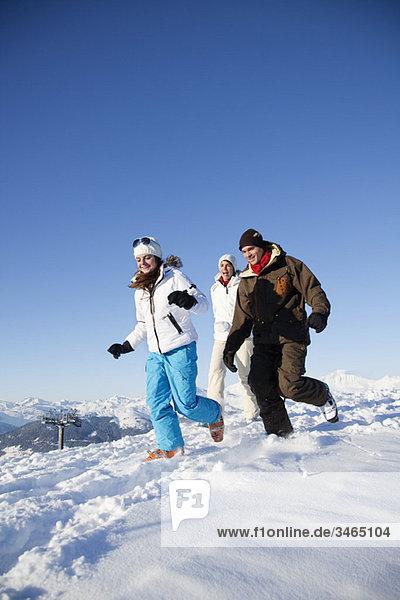 Paar und Tochter in Skibekleidung laufen im Schnee