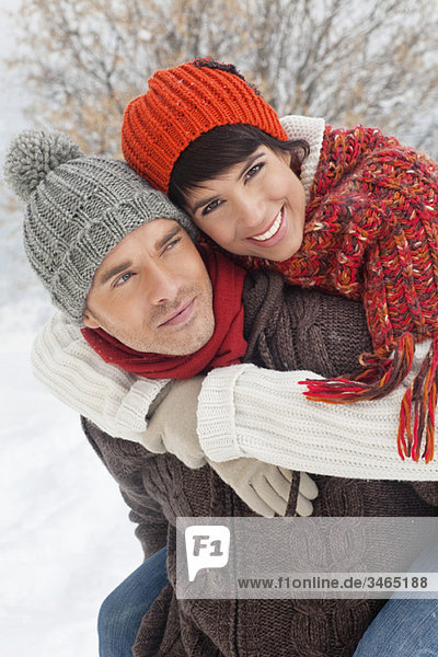 Junger Mann gibt seiner Freundin Huckepack im Schnee