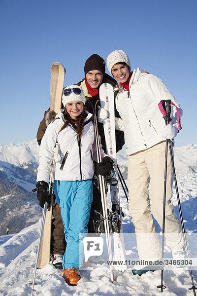 Paar und Tochter halten Skier  lächeln vor der Kamera
