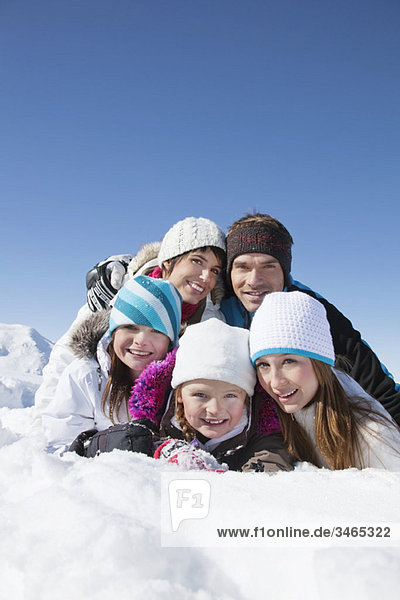 Glückliche Familie im Schnee liegend  lächelnd vor der Kamera