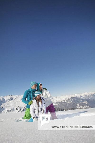 Paar und Tochter in Skibekleidung  wegblickend