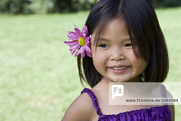 A young girl with a flower behind her ear