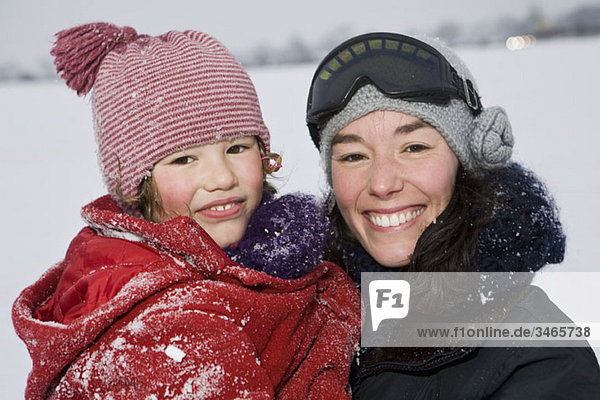 A woman holding her daughter  outdoors  portrait