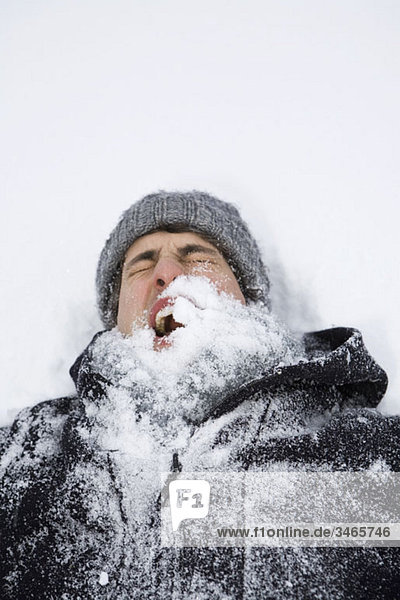 A man lying on back after being hit with a snowball  head and shoulders
