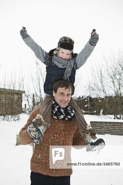 Ein Mann  der seinen Sohn auf den Schultern trägt.