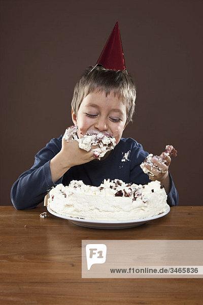 Ein Junge mit einem Partyhut  der Geburtstagskuchen mit den Händen isst  Atelieraufnahme