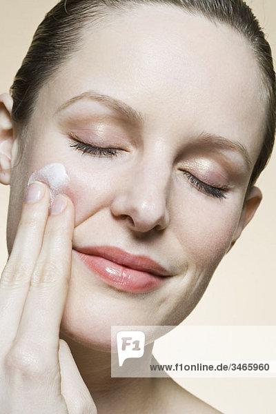 Eine ruhige Frau  die Feuchtigkeitscreme auf ihre Wange aufträgt.