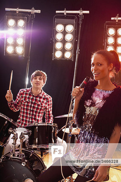 A woman singer accompanied by a man on drums performing on stage