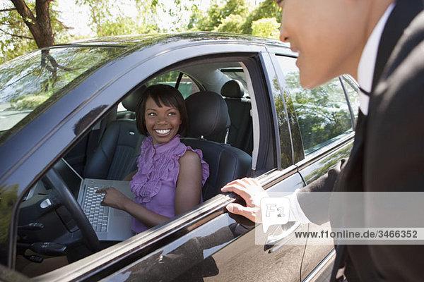 Eine Frau  die in einem Auto sitzt und einen Laptop hält und mit einem Mann außerhalb des Autos redet.