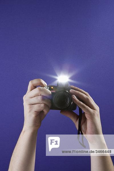 Detail eines Mannes  der mit einer Kamera fotografiert.
