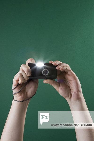 Detail eines Mannes  der mit einer Digitalkamera fotografiert.