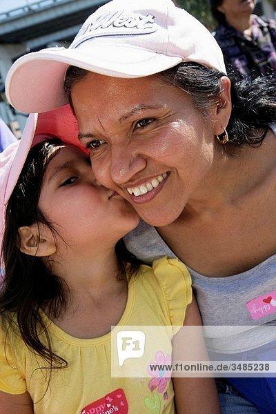 Florida  Miami  Little Havana  Jose Marti Park  United Hearts Family Festival  community event  Hispanic  woman  girl  mother  daughter  parent  child  smiling  kissing