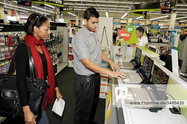 Florida  Miami  Staples  office supply products store  retail  business  chain  merchandise  display  laptop  computer  Hispanic  Black  man  woman  sales clerk  job  employee  customer  shopping