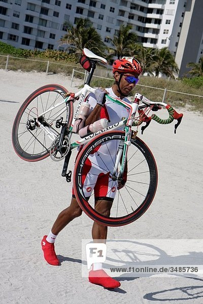 Florida  Miami Beach  Nautica South Beach Triathlon  Atlantic Ocean  shore  sport  fitness  race  bike  bicycle  segment  cyclist  athlete  competitors  Black  man  transition  helmet  sports eyeglasses  carry on shoulder  competition  race