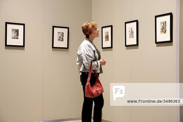 Michigan  Saginaw  Saginaw Art Museum  education  exhibit  collection  woman  middle-aged  red hair  looking  framed prints  profile  gallery