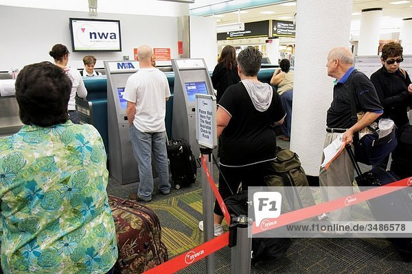 Florida  Miami  Miami International Airport  Northwest Airlines  NWA  carrier  ticket counter  line  queue  man  woman  passenger  waiting  luggage  ticketing  check-in kiosk  terminal