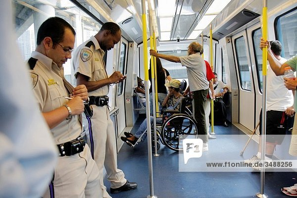 Florida  Miami  Metromover  public transportation  mass transit  automated people-mover  passenger  Black  Hispanic  man  woman  security guard  safety  writing  wheelchair  standing  Wackenhut